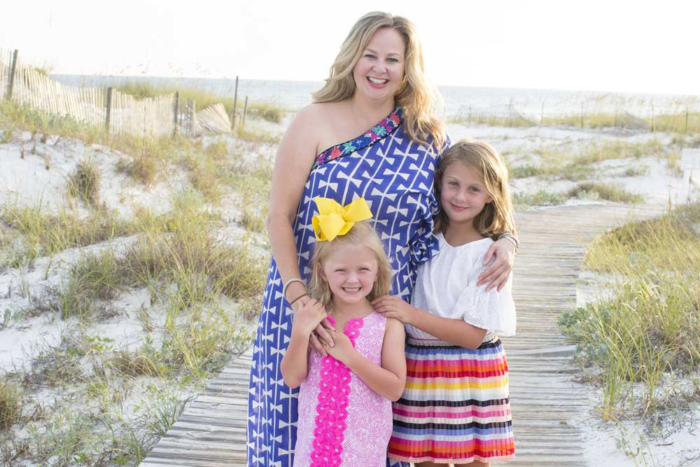 adrianne graves in dress standing on beach with two young daughters