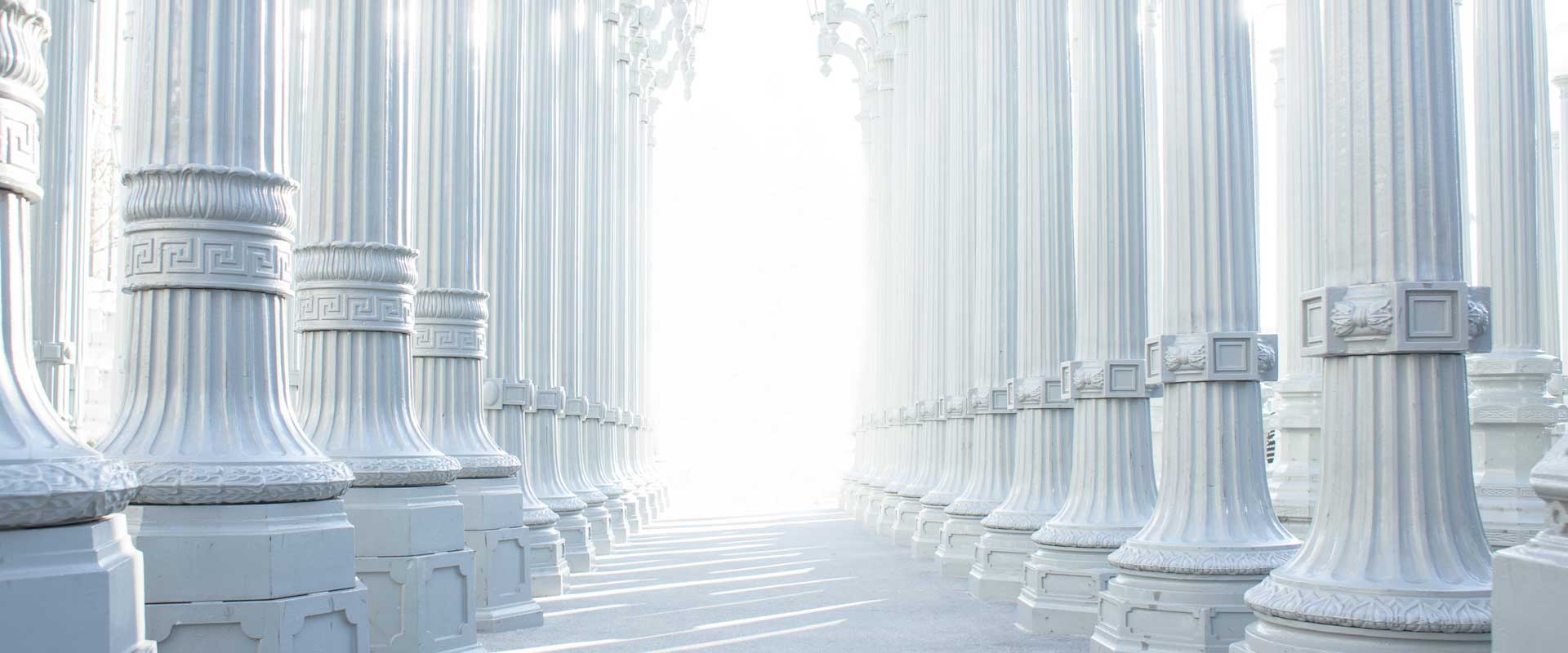 many rows of white pillars with bright white light in the distance