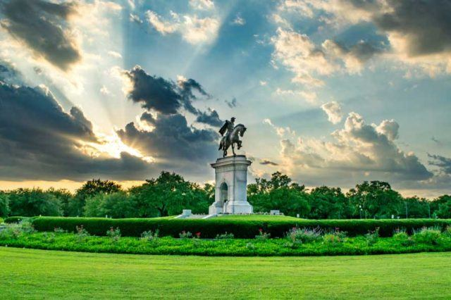 hermann park statue in houston with sun peeking through clouds in the sky