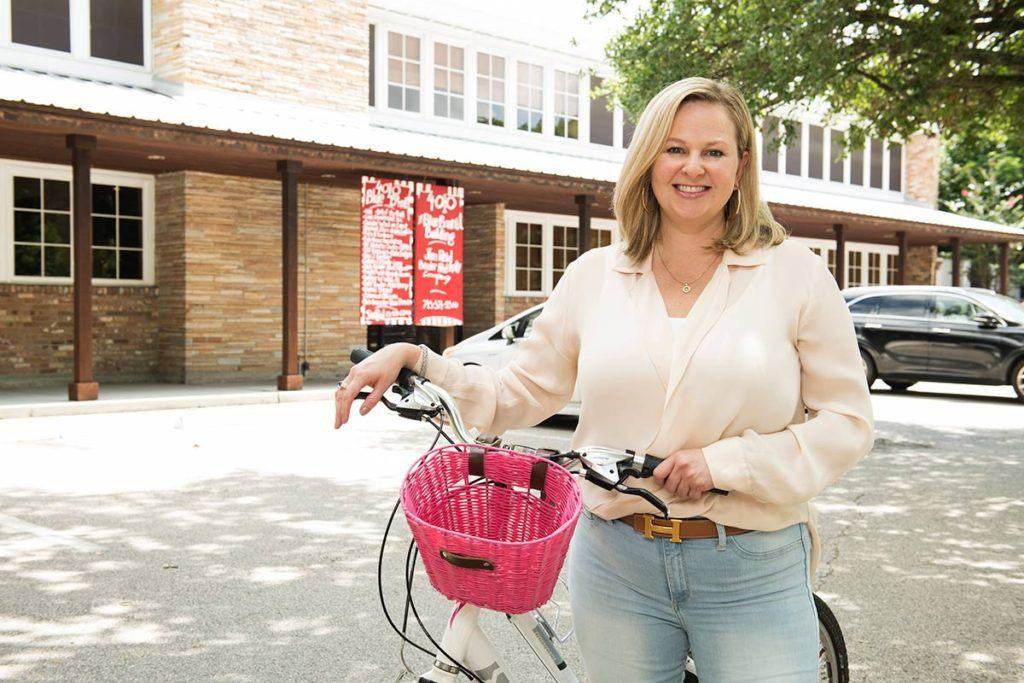 adrianna graves standing with bike with pink basket outside